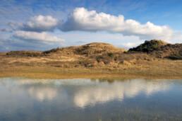 Weerspiegeling van rij witte wolken in natte duinvallei 'Grote Pan' op zonnige dag in het Nationaal park Zuid-Kennemerland bij Bloemendaal aan Zee - © Ronald van Wijk Natuurfotografie