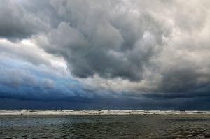 Donkere, dreigende wolkenlucht tijdens storm boven zee op het strand van Wijk aan Zee.