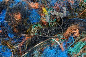 Opeenstapeling aan aangespoelde visnetten aan de rand van de sluftergeul in het Nationaal Park Duinen van Texel