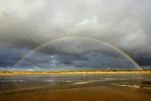 Regenboog en donkere lucht van regenbui boven het uitgestrekte strand en de duinen van het Kennemerstrand bij IJmuiden.