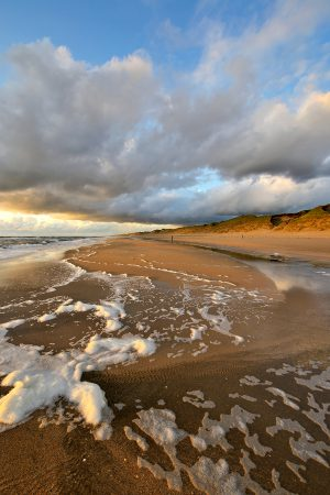 Warm licht van zonsondergang schijnt op wolkenlucht boven de zee en het strand van Heemskerk.