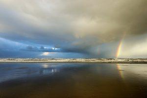 Een regenboog aan de onderkant van een hagelbui boven de Noordzee op het Kennemerstrand bij IJmuiden.
