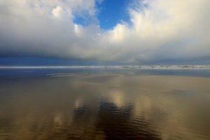 Weerspiegeling van wolkenlucht boven zee in het ondiepe water langs de vloedlijn op het Kennemerstrand bij IJmuiden.