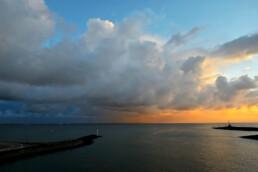 Uitzicht vanaf de veerboot naar Texel op warm licht van zonsopkomst op grote wolkenlucht van bui boven de Waddenzee - © Ronald van Wijk Natuurfotografie