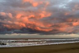Warm, roze licht van de zon schijnt op een wolkenlucht boven zee tijdens zonsopkomst op het strand van Bloemendaal aan Zee - © Ronald van Wijk Natuurfotografie