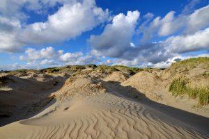 Blauwe lucht en witte wolken boven de zeeduinen op het Kennemerstrand bij IJmuiden.