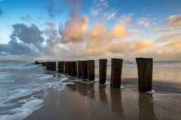 Weerspiegeling van warm zonlicht op wolken boven rij houten palen van paalhoofd tijdens zonsopkomst op het strand bij Schoorl - © Ronald van Wijk Natuurfotografie