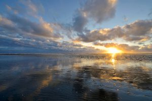 Zonlicht breekt door de wolken tijdens zonsondergang langs de vloedlijn op het Kennemerstrand bij IJmuiden