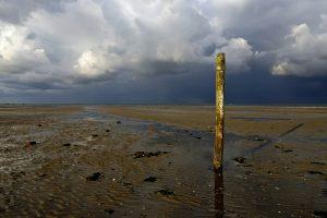 Donkere, dreigende wolkenlucht van hagelbui boven de Waddenzee bij vogelreservaat De Volharding op Waddeneiland Texel