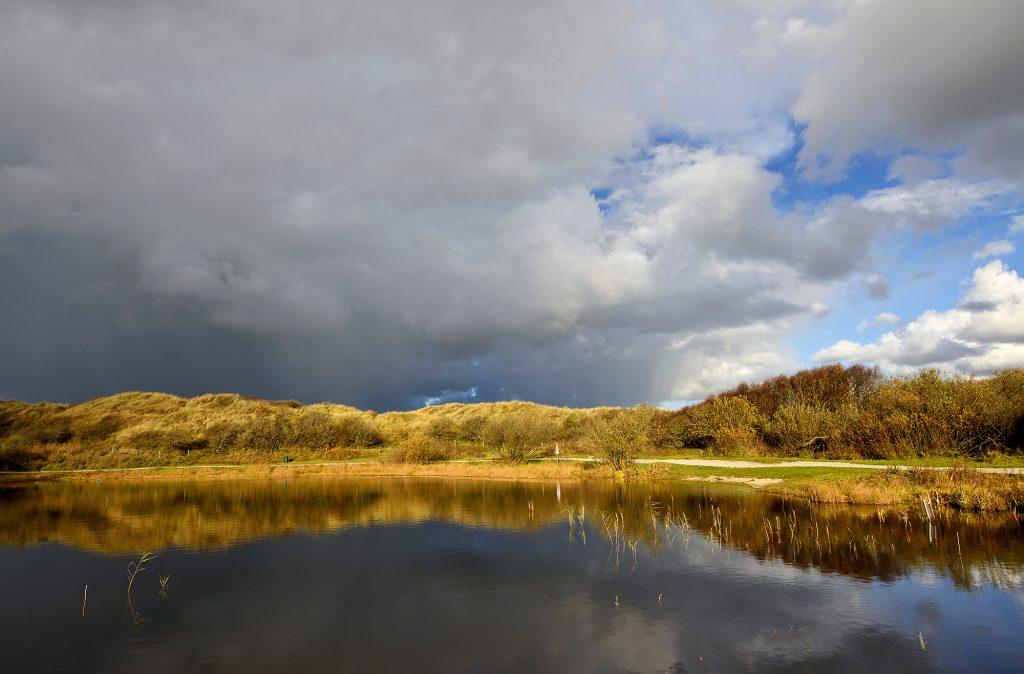 Donkere wolkenlucht van regenbui weerspiegelt in het stille water van een duinmeer in de Pettermerduinen bij Petten.