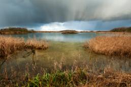 Wolken van regenbui boven het hoefijzermeer in het infiltratiegebied van het Noordhollands Duinreservaat bij Castricum