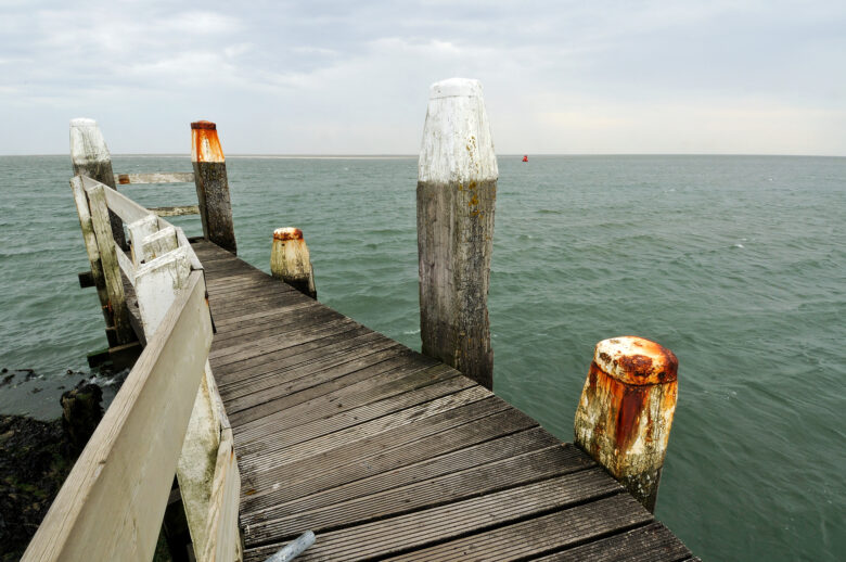 Verweerde, houten steiger tijdens onstuimige, bewolkte dag in de haven van het Waddeneiland Vlieland.