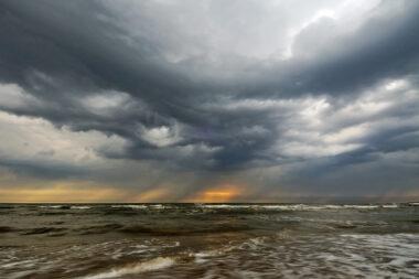 Donkere wolk van naderende hagelbui boven de Noordzee tijdens storm op het Kennemerstrand bij IJmuiden.