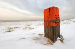 Houten strandpaal met oranje verf en gekerfde zwarte letters tussen besneeuwde, witte duinen op het Kennemerstrand bij IJmuiden.