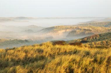 Uitzicht op duinlandschap met laagjes mist tussen de duinhellingen tijdens zonsopkomst in de duinen bij Egmond-Binnen.