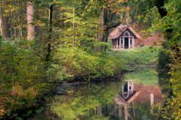 Doorkijkje naar een weerspiegeling van prieeltje in het water van beek tijdens de herfst op Landgoed Elswout in Overveen.