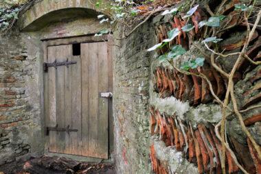 Een met dakpannen beklede muur leidt naar ingang van de ijskelder op het Landgoed Elswout in Overveen.