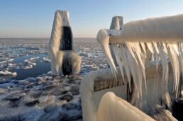 IJspegels hangen aan het hek van een bevroren steiger tijdens een koude winterdag op het IJsselmeer bij Den Oever.