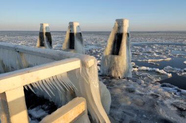 IJspegels hangen aan het hekwerk van een steiger met uitzicht op drijvende ijsschotsen tijdens winter op het IJsselmeer.
