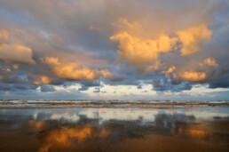 Warm licht van de zonsopkomst weerspiegelt op wolkenlucht boven zee op het Kennemerstrand bij IJmuiden.