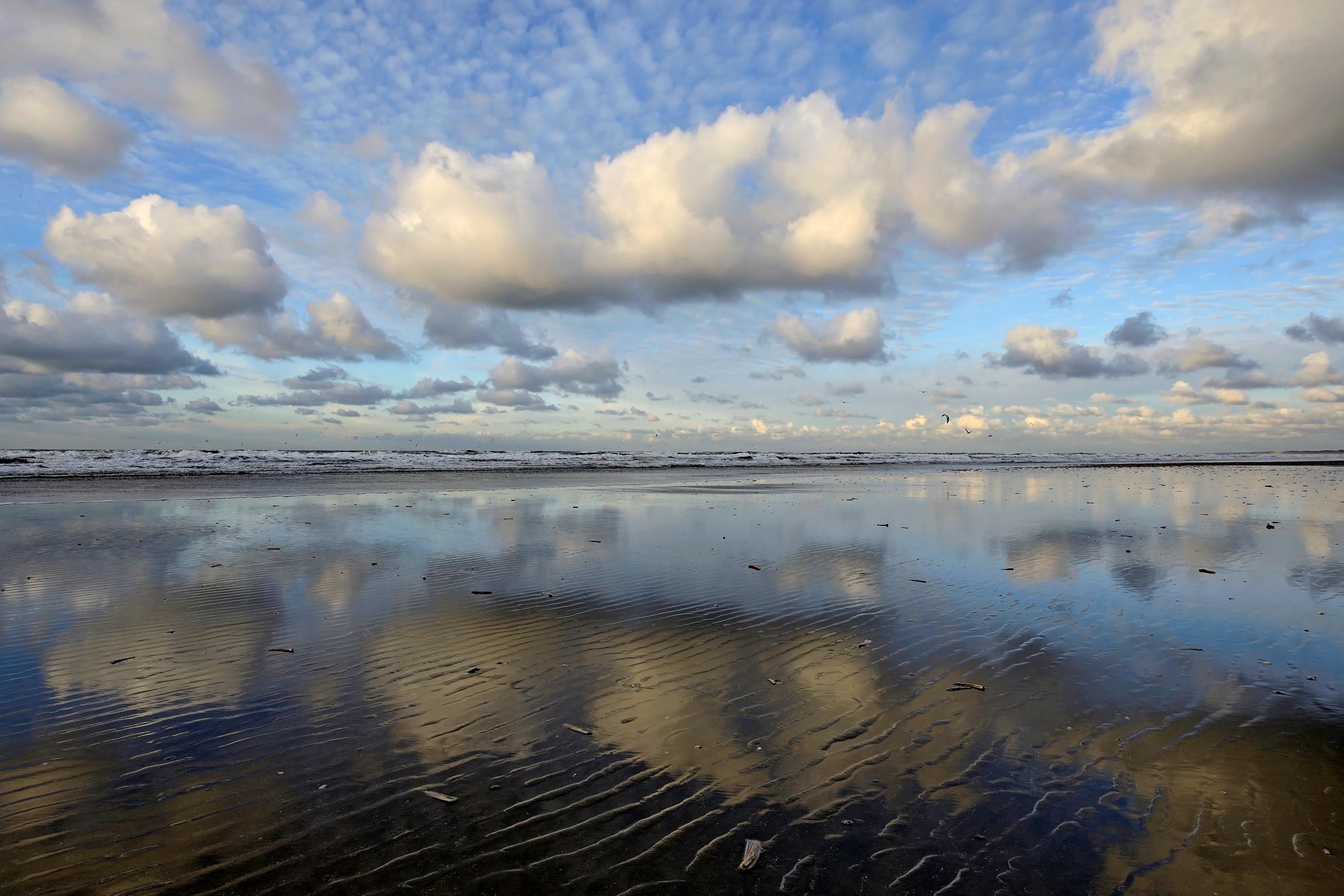 Weerspiegeling van rij wolken in ondiep zeewater langs de vloedlijn op het strand van Wijk aan Zee