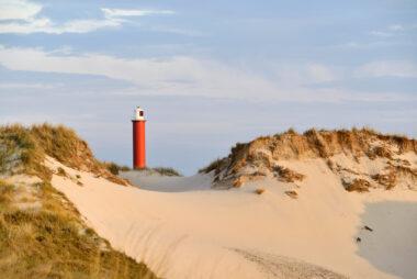 Warm zonlicht schijnt op zanderige duinhelling en rode vuurtoren Groote Kaap in de Noordduinen bij Julianadorp aan Zee.