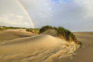 Regenboog boven het strand en de eerste rij zeeduinen na een regenbui op het Kennemerstrand bij IJmuiden.