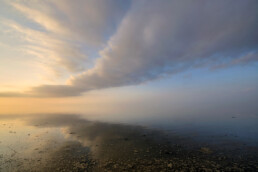 Weerspiegeling van wolkenlucht in het ondiepe water van de Waddenzee tijdens zonsondergang op Wieringen.
