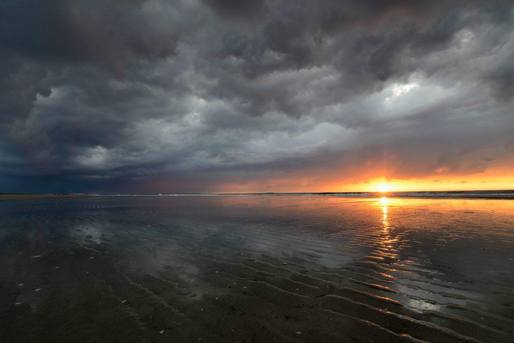 Laatste zonnestralen schijnen over het natte zand bij de vloedlijn tijdens zonsondergang met dreigende wolkenlucht op het strand van Wijk aan Zee