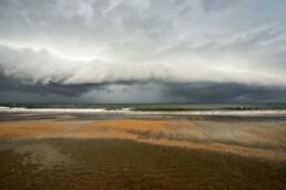Grote, dreigende rolwolk nadert het land vanuit zee tijdens storm op het strand van Heemskerk.