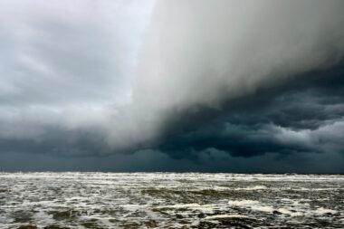 Donkere, dreigende wolkenlucht van hagelbui nadert vanaf zee het strand tijdens storm bij Castricum aan Zee.