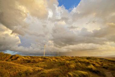 Wolkenlucht boven de zeeduinen en windmolens tijdens storm op het strand van Wijk aan Zee