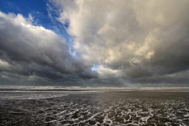 Grote wolkenluchten worden door de wind over de zee geblazen tijdens storm op het strand van Wijk aan Zee