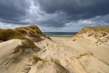 Donkere wolken boven een grote kerf in de zeeduinen van het Noordhollands Duinreservaat op het strand van Heemskerk.