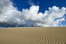 Blauwe lucht en wolken boven slingerende zandribbels over duinhelling van een groot stuifduin in het Nationaal Park Zuid-Kennemerland bij IJmuiden