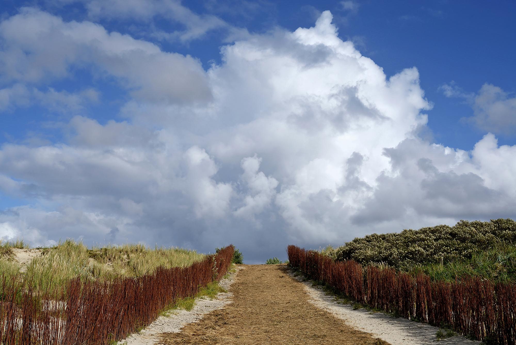Blauwe lucht en witte wolken boven het zandpad van de opgang naar het Westerstrand op het waddeneiland Schiermonnikoog
