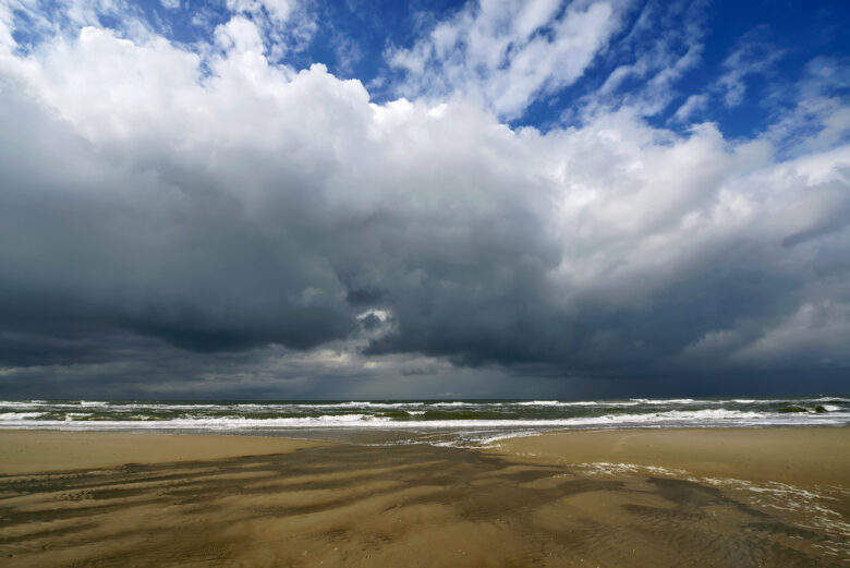 Grote, donkere wolkenlucht van naderende bui boven de Noordzee op het strand van het Waddeneiland Texel.