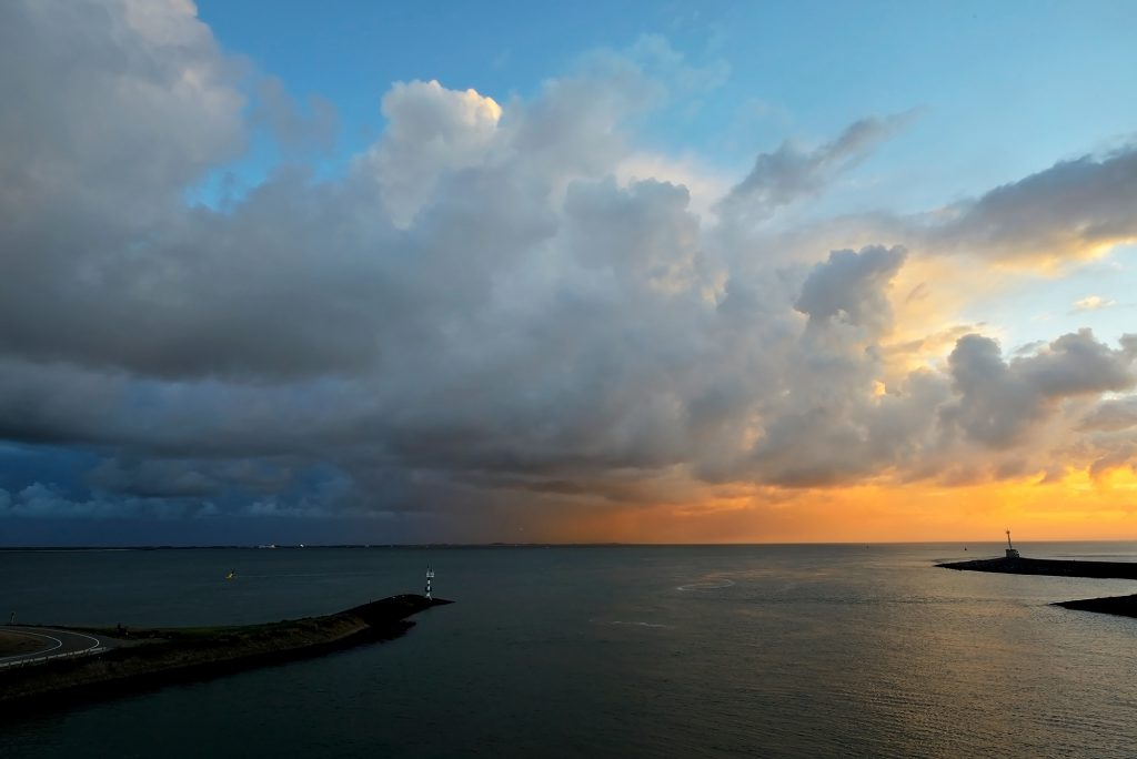 Uitzicht vanaf de veerboot naar Texel op warm licht van zonsopkomst op grote wolkenlucht van bui boven de Waddenzee