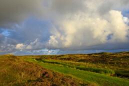 Wolken en regenboog boven wandelpad langs de Moksloot in het Nationaal Park Duinen van Texel bij Den Hoorn.