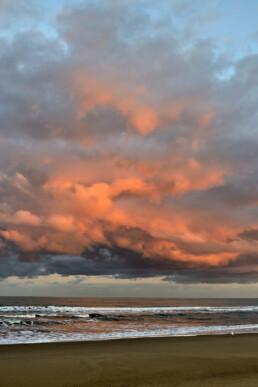 Warm, roze licht van de zon schijnt op een wolkenlucht boven zee tijdens zonsopkomst op het strand van Bloemendaal aan Zee.