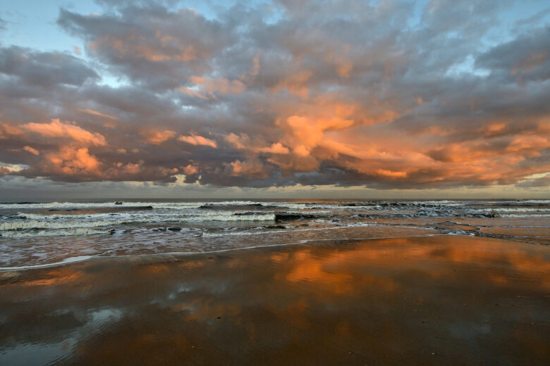 Warm, roze licht van de zon schijnt op een wolkenlucht boven zee tijdens zonsopkomst op het strand van Bloemendaal aan Zee