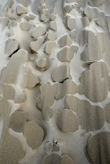 Uitgeslepen zandvormen in een groot stuifgat in de duinen na een storm op het strand van Heemskerk