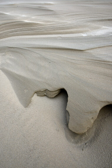 Door de wind uitgekerfde vormen en lijnen in het zand van de helmduinen na storm op het strand van Wijk aan Zee.