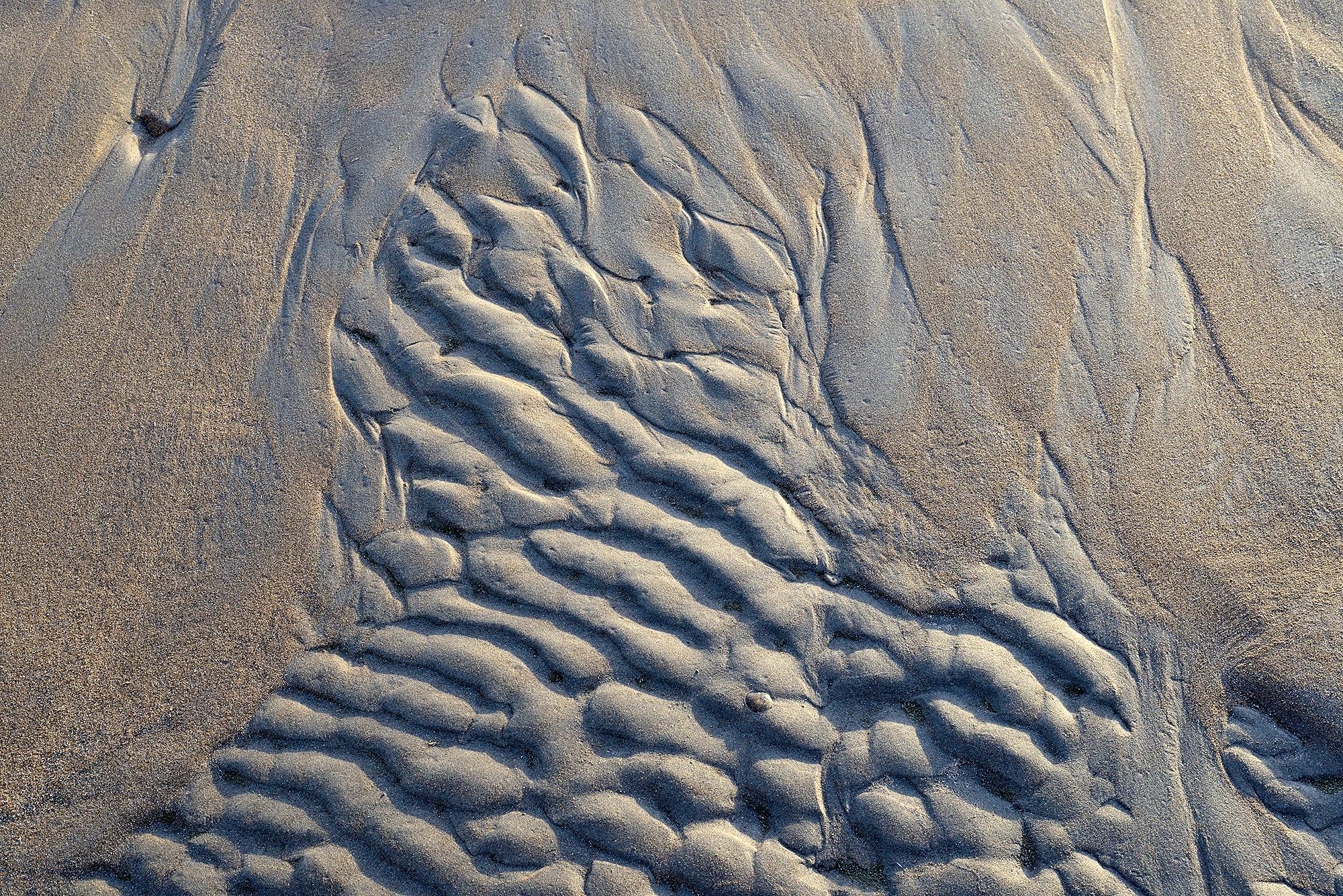Zandribbels van terugtrekkend zeewater aan de rand van een zwin tijdens laagwater op het Kennemerstrand bij IJmuiden.