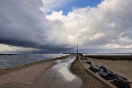 Donkere wolkenlucht van een regenbui strekt zich uit boven het strand en het betonnen pad van de Noordpier bij Wijk aan Zee.