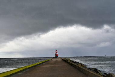 Donkere wolkenlucht van regenbui boven rood met wit gestreept lichthuis aan het einde van de Noordpier bij Wijk aan Zee.