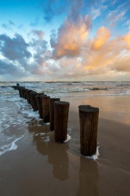 Weerspiegeling van warm zonlicht op wolken boven rij houten palen van paalhoofd tijdens zonsopkomst op het strand bij Schoorl