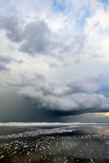 Donkere, dreigende wolkenlucht van naderende hagelbui boven zee tijdens storm op het strand van Wijk aan Zee