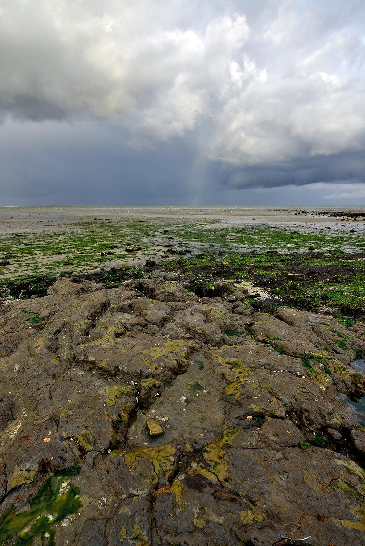 Donkere, dreigende wolkenlucht van regenbui boven de Waddenzee bij vogelreservaat De Volharding op Waddeneiland Texel.