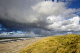 Donkere lucht van regenbui boven strand, duinen en zee in de Noordduinen ten noorden van Callantsoog